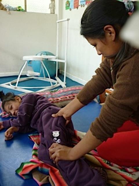 Guadalupe pratique le shiatsu avec sa petite soeur, atteinte de paralysie cérébrale infantile.